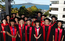 Doctoral graduates with Rangitoto in the background