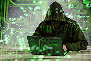 Hooded person hacking into web security