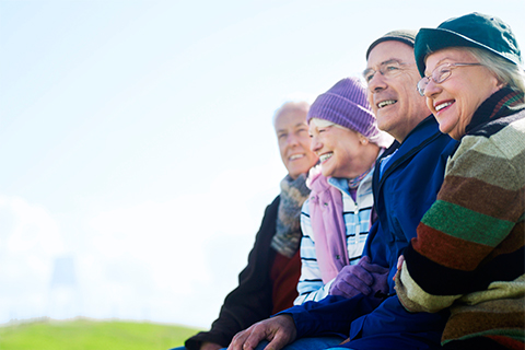 Four older people sitting on bench