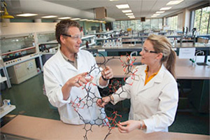 Massey chemistry lecturer and student in laboratory inspecting model