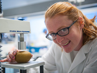 Scientist with kiwi fruit in lab