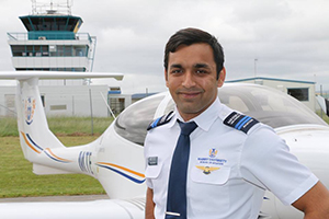 Arjun Jethmal standing in front of a plane on the tarmac