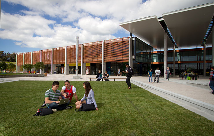 Students relaxing outside on the grass in front of large building