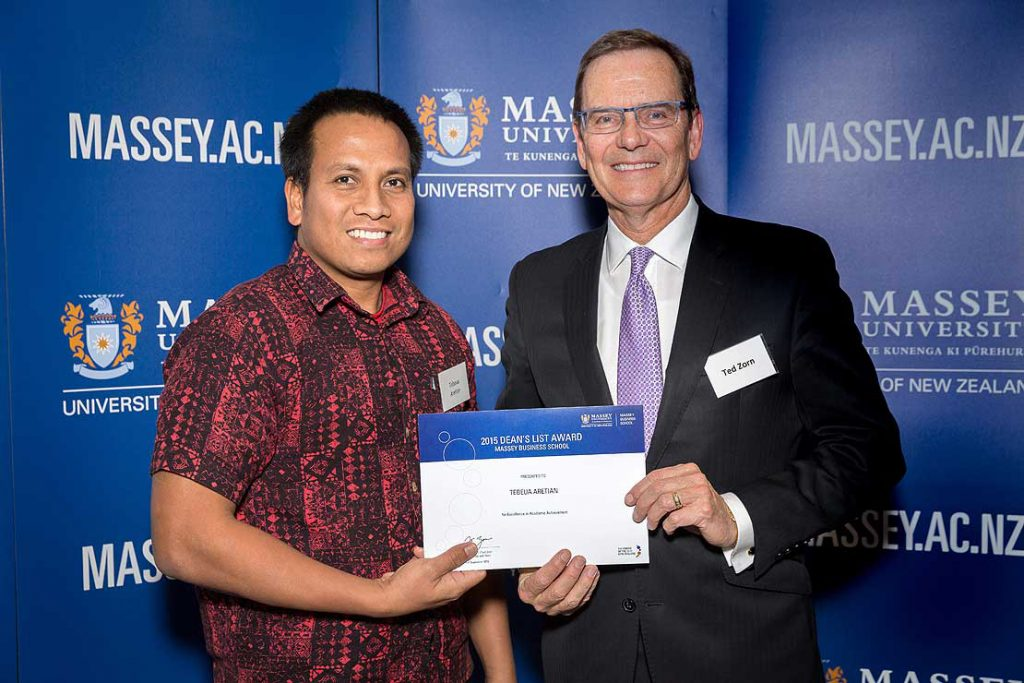Student receiving Dean's List certificate from head of Massey Business School